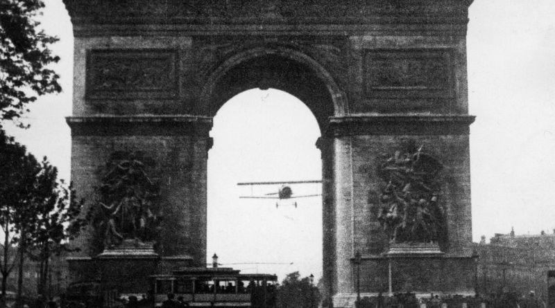 Un avion passe sous l'Arc de Triomphe
